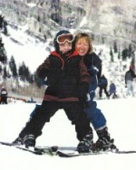 Adult behind child doing adaptive skiing with a snowy mountain background