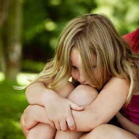 Anxiety in children - young girl hugging knees anxiously