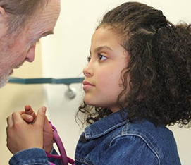 A young girl with thick, black hair  and a jean jack makes eye contact with an elderly man and displays stereotypical hand behavior