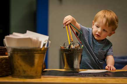 Child placing colored pencils into a bucket